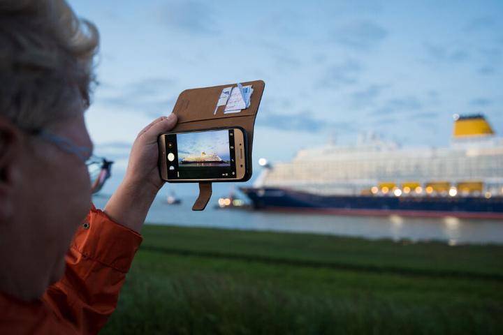 Eine Frau verfolgt die Fahrt des Schiffs und macht ein Foto des Kreuzfahrtriesens mit ihrem Smartphone.
