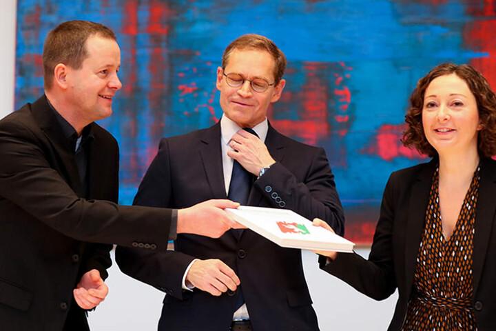 Klaus Lederer (Linke) (l-r), Berlins Regierender Bürgermeister Michael Müller (SPD) und die Ramona Pop (Grüne), tauschen nach der Unterzeichnung den Koalitionsvertrag von SPD, Linken und Grünen.
