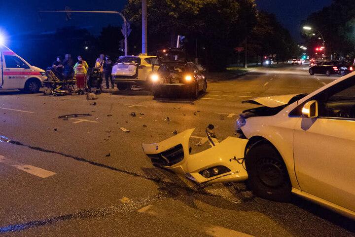 Die Kreuzung ist übersät von Trümmerteilen, die Folgen des Unfalls an den Fahrzeugen sind deutlich zu erkennen.
