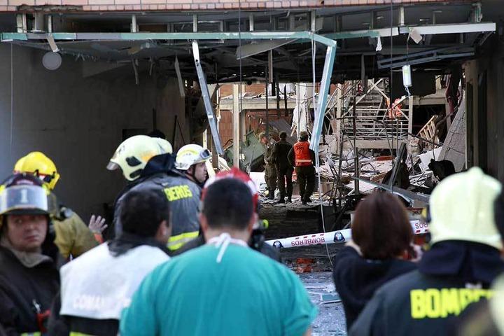 Rettungskräfte an der Unglücksstelle, im Hintergrund sind die Trümmer des Krankenhauses zu sehen.