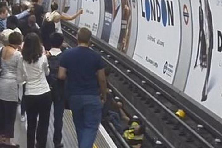 Die Passanten schauen zu, als der Retter auf die U-Bahn-Gleise springt, um den Mann zu retten.