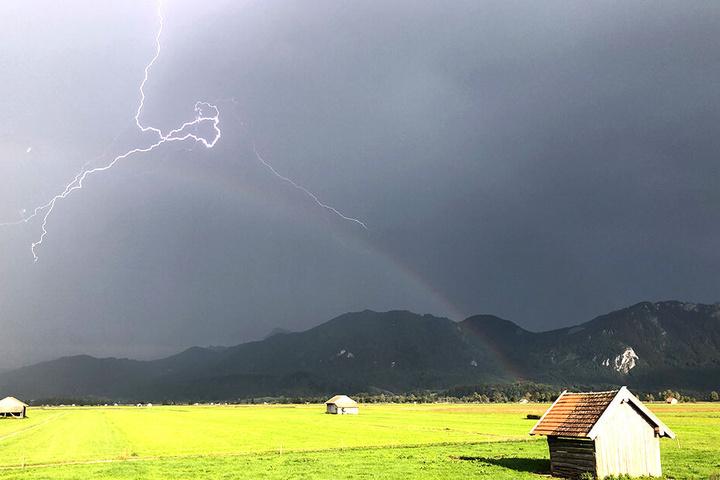 Gewitter und Blitze vor einem bayrischen Bergdorf.