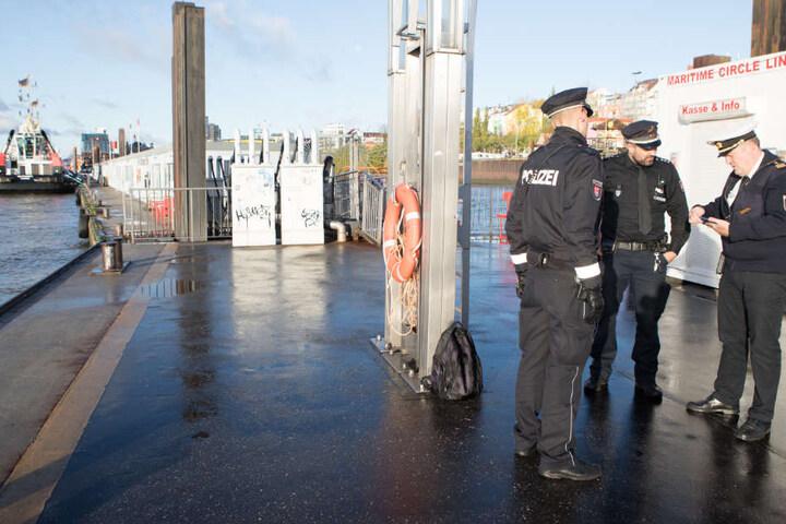 Beamte stehen an einem Anleger an den Landungsbrücken: Hier wurde der Mann aus dem Wasser gezogen.