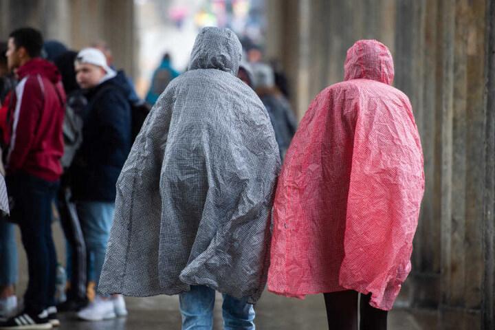 Touristen schützen sich in Regencapes vor den Niederschlägen.