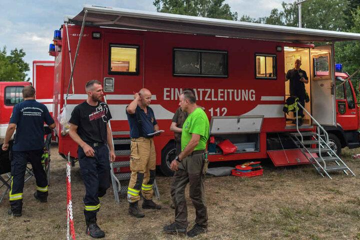 Die Einsatzleitung der Feuerwehr steht am späten Abend auf einem Dorfplatz in Byhleguhre am Rande des Spreewaldes.