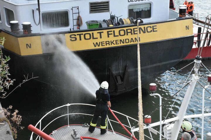 Feuerwehrleute löschen den Schiffsbrand.