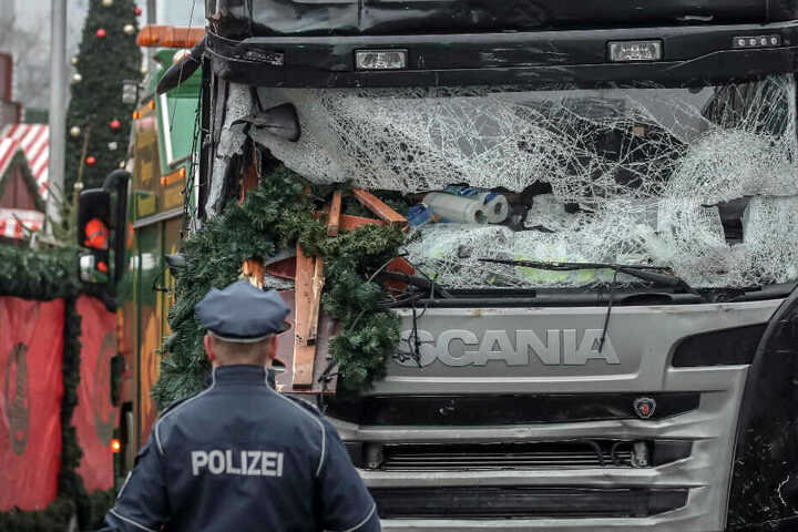 Ein Polizist steht vor dem Lastwagen, mit dem Attentäter Amri über den Weihnachtsmarkt gefahren ist.