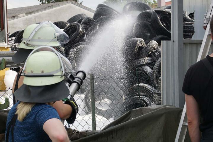 Einsatzkräfte versprühen Schaum, um ein Übergreifen der Flammen zu verhindern.