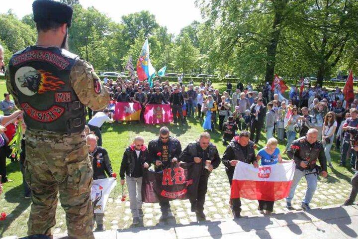 Mit roten Nelken, Fahnen und vielen Schaulustigen am Dresdner Denkmal.