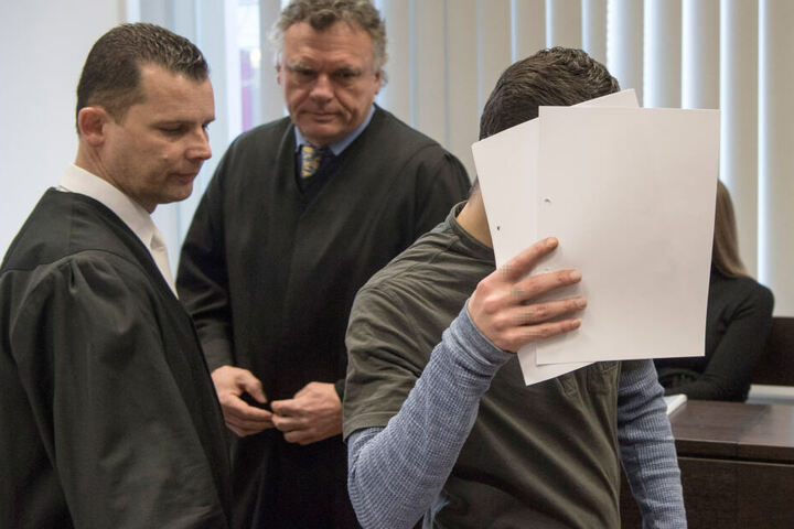 Der Angeklagte versteckt sein Gesicht.