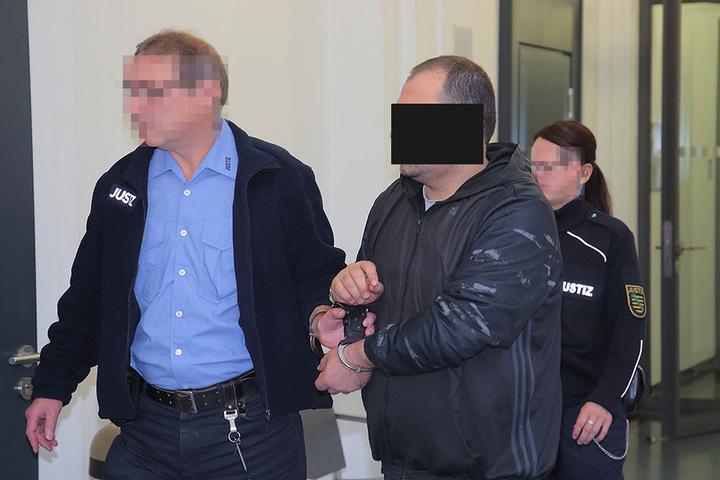 Hier wird einer der sechs Angeklagten zum Prozess gebracht.