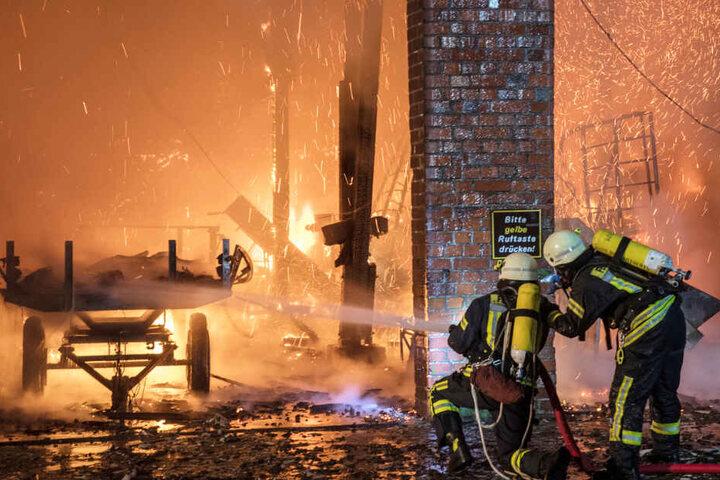 Feuerwehrleute spritzen Wasser in die brennende Scheune.