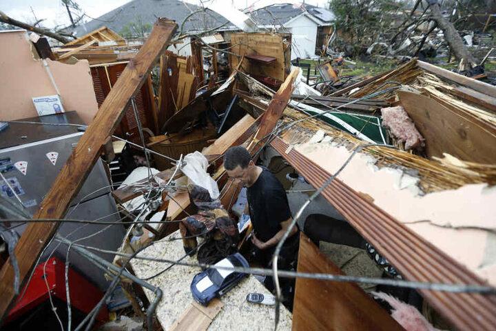 Ein Mann sucht in den Trümmern seines Hauses nach seiner Brille.