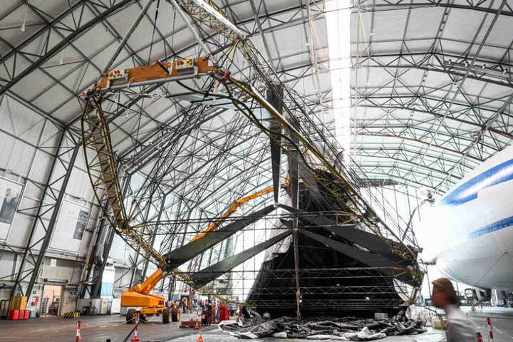 Besucher sehen sich den im Wiederaufbau befindlichen Zeppelin an.