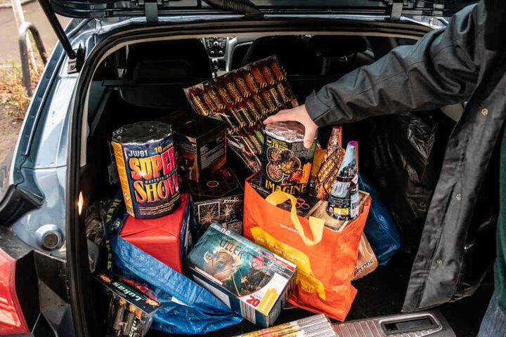 Ein Mann zeigt Böller und Silvesterraketen, die er in einem Geschäft in Friedrichshain gekauft hat.