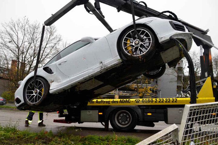 Porsche flieg: Am Kranhaken des Abschleppwagens wird der demolierte Flitzer nach oben gehievt.