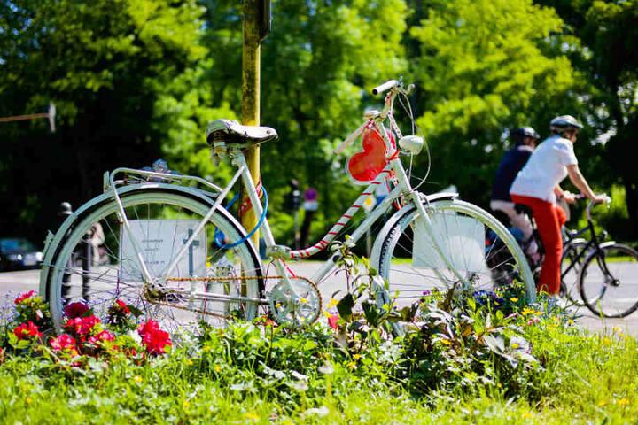 Ein geschmücktes Fahrrad steht an einer Kreuzung in Köln. Hier war im Jahr 2011 eine junge Radfahrerin bei einem Verkehrsunfall tödlich verletzt worden.