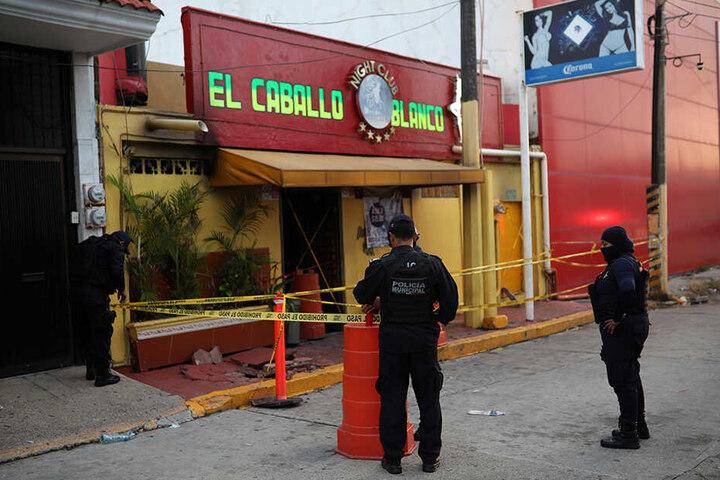 """Polizeibeamte stehen vor der Bar """"El caballo blanco"""" in Coatzacoalcos und sichern den Tatort."""