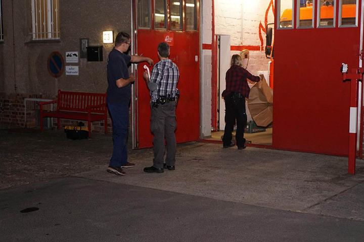 Einer der Feuerwehrmänner beschreibt einen Kripo-Beamten den Tathergang, während eine Kollegin Einbruchswerkzeug aus einer Tüte auspackt.