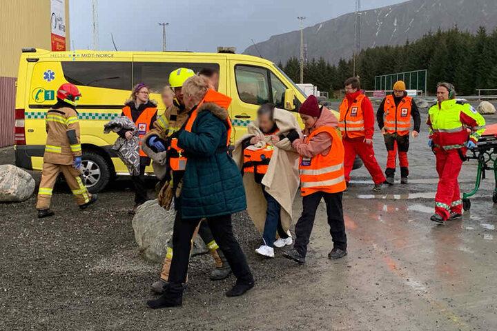 Passagiere des Kreuzfahrtschiffes werden in eine Notunterkunft gebracht, nachdem sie mit einem Hubschrauber vom Schiff geholt wurden.
