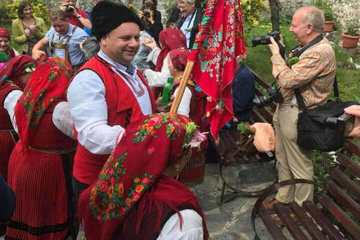 """Zum Willkommen schwenken die Dorffrauen eine bunte """"Fahne"""" und stimmen ein Volkslied an."""
