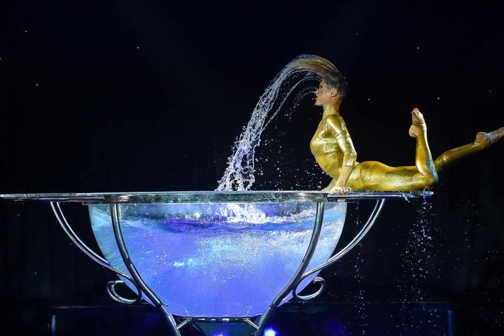 """Spritzig: Artistin Katrina Asfardi """"badet"""" in einer mit Wasser gefüllten  Halbkugel."""