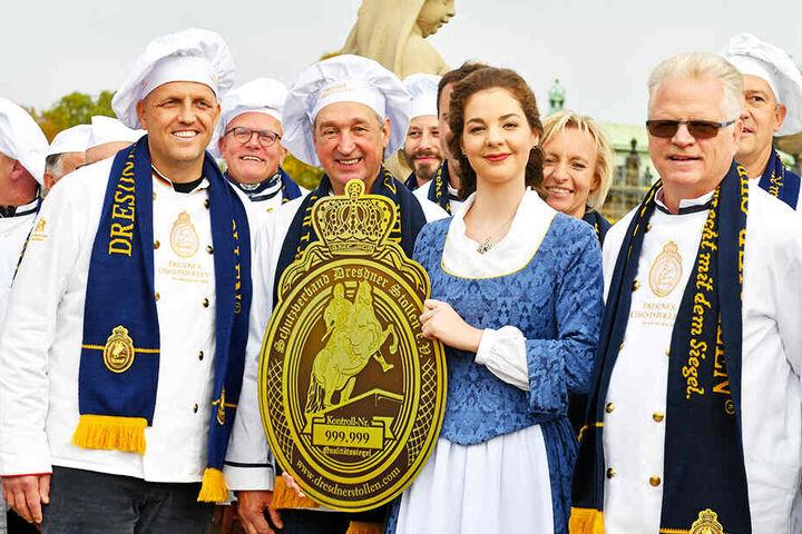 Die Dresdner Bäckermeister Rene Krause (43, l.), Reiner Israel (66, 2.v.l.) und Mühlenbäcker-Chef Volker Beduhn (61, r.) drängeln sich um ihr schönes Dresdner Stollenmädchen Veronika Weber (23).