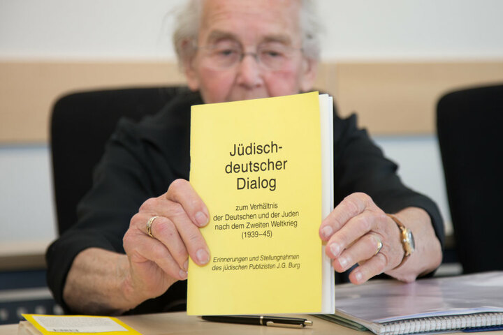 """Die Angeklagte Ursula Haverbeck hält im September vor gericht ein Buch mit dem Titel """"Jüdisch-deutscher Dialog"""" in den Händen."""