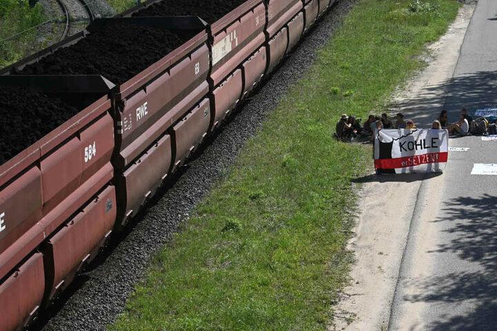 Auf den Bahnschienen neben der Blockad fährt ein Kohlezug der RWE.