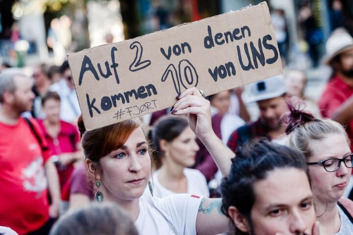 """Eine Demonstrantin hält ein Schild mit der Aufschrift """"Auf 2 von denen kommen 10 von UNS """" hoch."""