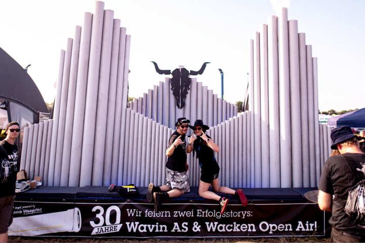 Zwei Wacken-Besucher lassen sich vor einer Holz-Skulptur fotografieren.