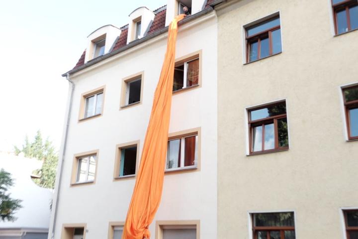 Hier wird die größte Blockfahne Europas aus einem Wohnhaus in Dresden herabgelassen.