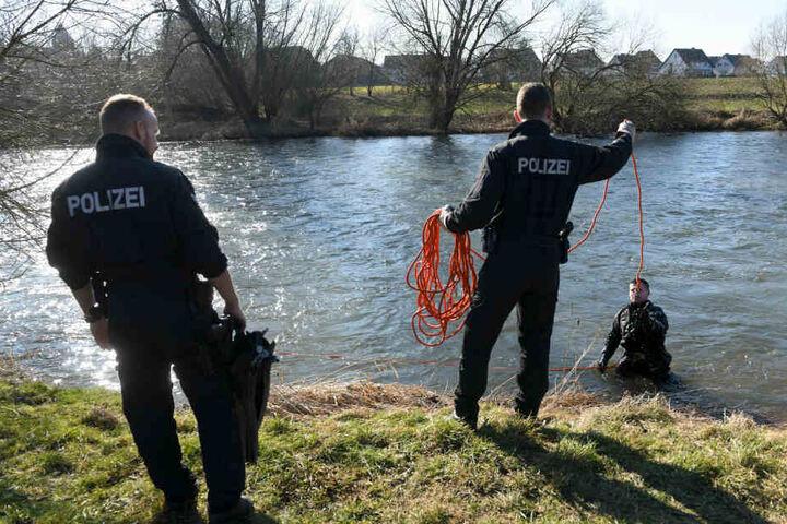 Polizeikräfte unterstützen einen Taucher, der den Uferbereich absucht.