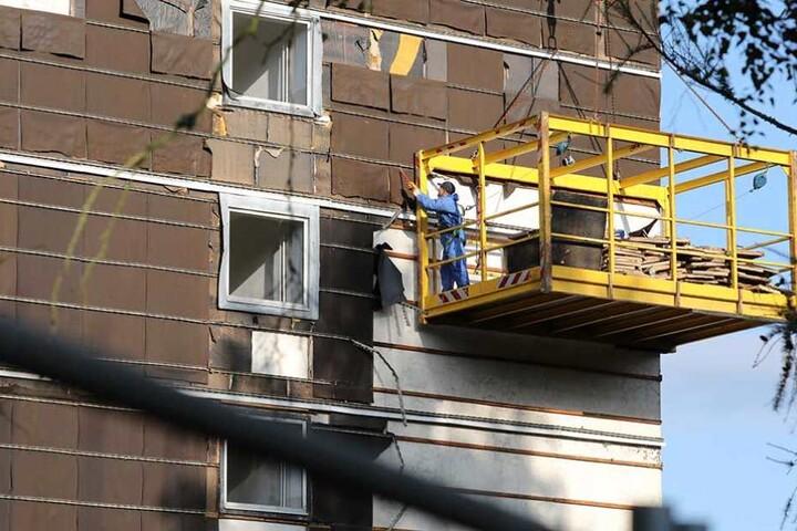 Ein Arbeiter ist damit beschäftigt, die Fassade des Hotels auf die Sprengung vorzubereiten.