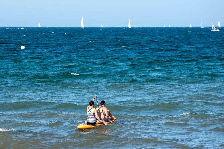 Zwei Frauen paddeln auf der Ostsee auf einem Stand-Up-Paddling-Board.