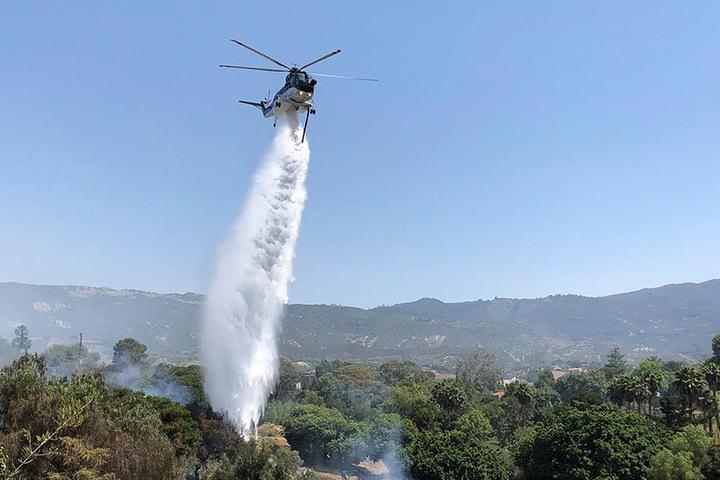 Mit Lösch-Helikoptern wird versucht, die brennenden Bereiche unter Kontrolle zu bringen.