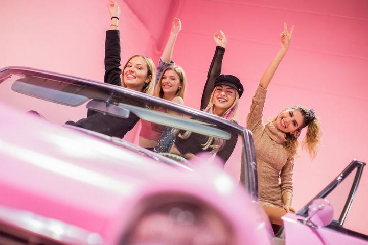 Models testen eine rosa Autokulisse in dem Museum.