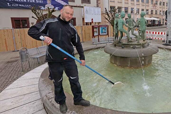 Martin Lang säubert mit einem Kescher den sprudelnden Kinderbrunnen in der City.