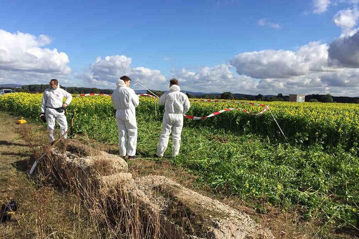 Spezialisten der Spurensicherung suchen die Tatwaffe - ein Messer - in einem Feld nahe des Tatorts.