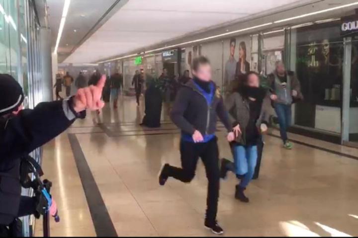 """In der Passage simulieren Polizisten die Einkaufenden, die vor den """"Terroristen"""" der Übung flüchten."""