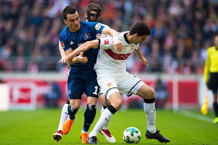 VfB-Innenverteidiger Marcin Kaminski (r.) im Zweikampf mit HSV-Flügelstürmer Filip Kostic (l.). Maskenmann Christian Gentner (hinten) greift unterstützend ein.