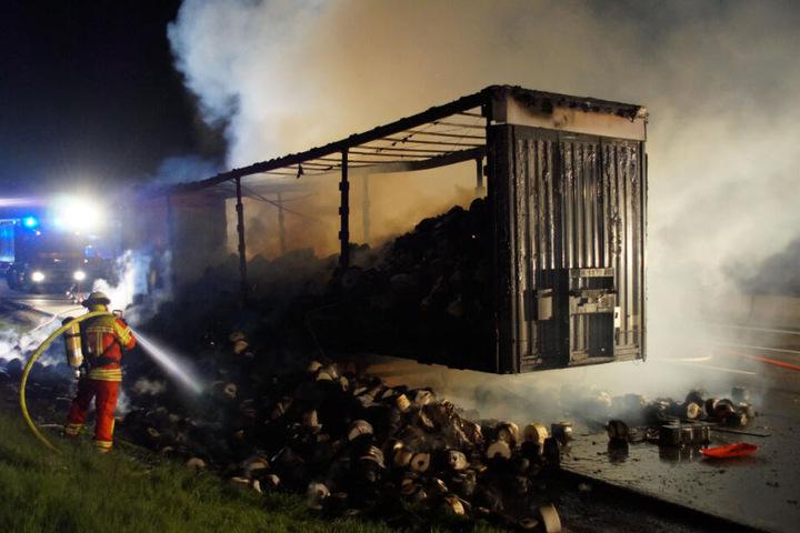 Ein Feuerwehrmann löscht den brennenden Lastwagen.