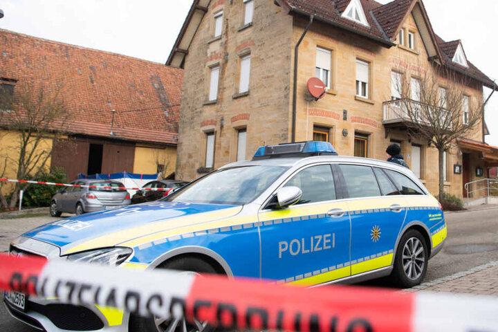 Am Tag nach der Tat steht ein Polizeiauto vor dem Haus hinter Absperrband.