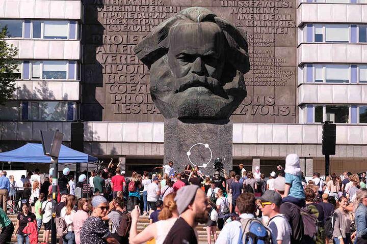 """Besucher des Festivals """"Kosmos Chemnitz - Wir bleiben mehr"""" stehen am Karl-Marx-Monument. Mit dem Festival soll erneut ein Zeichen für eine friedliche, weltoffene Gesellschaft gesetzt werden."""