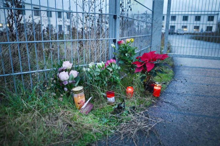 Blumen und Kerzen am Eingang zu einer kommunalen Unterkunft. (Archivbild)
