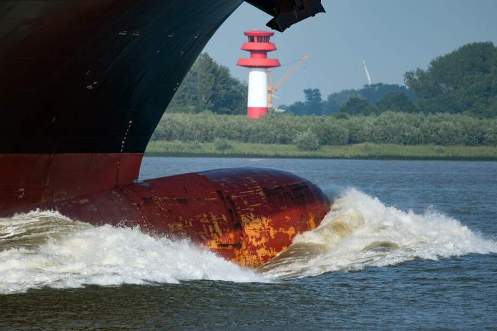 Der Bug eines Containerfrachters schiebt vor der Hafeneinfahrt in Hamburg eine große Welle vor sich her.