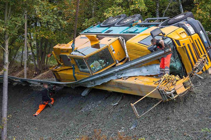 Der Kranwagen hat die Leitplanke durchbrochen und droht einen Abhang hinabzustürzen.