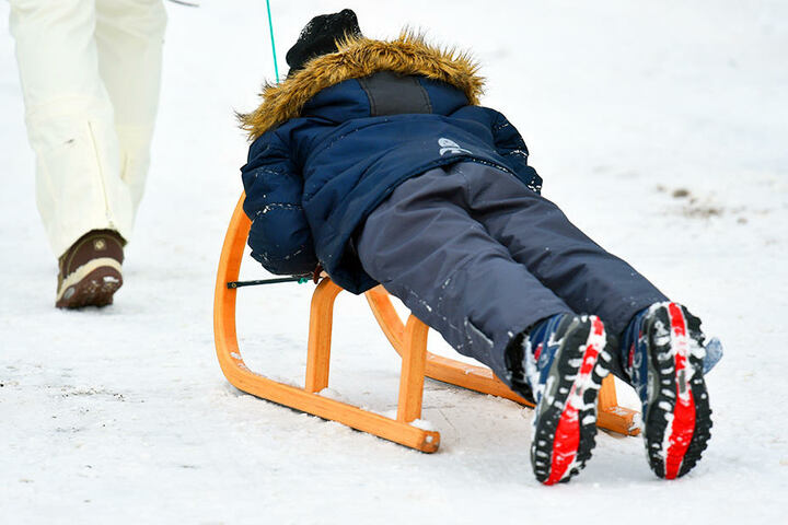 Ein Kind liegt auf einem Holzschlitten und lässt sich ziehen.