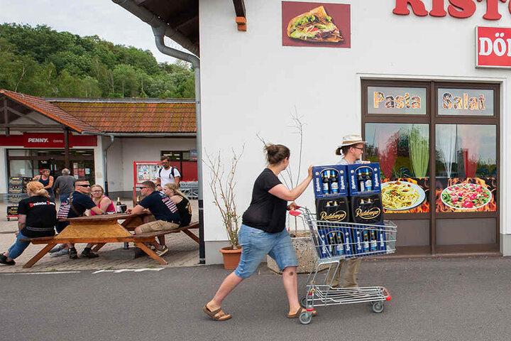 Eine Frau und ein Mann schieben einen Einkaufswagen mit Bier die Straße entlang.