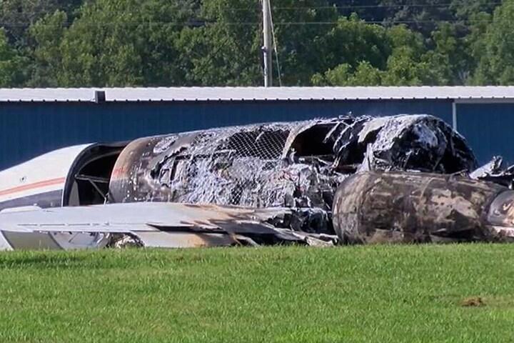 Die verbrannten Überreste des Flugzeugs liegen neben der Landebahn.